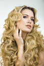 Beauty blond woman with long curly hair close up isolated Stock Images