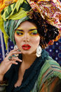 Beauty bright woman with creative make up, many shawls on head like cubian, ethno look closeup Royalty Free Stock Photo