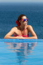 Beauty bronzed poolside girl woman in red young brunette bikini flower hair and glasses sunbathing on the edge of the infinity Royalty Free Stock Image