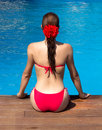 Beauty brunette girl sitting on edge of swimming pool a young woman with a red bikini and a flower in hair the a backward Royalty Free Stock Image