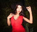 Beauty brunette women in red dress & hat pose at night park. Royalty Free Stock Photo