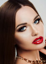 Beauty close-up portrait of young woman with bright makeup, blue eyes and red plump lips. Makeup, beauty, gold. Jewelry Royalty Free Stock Photo