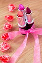 Beauty cosmetics: lipsticks, bow and flowers Royalty Free Stock Photography