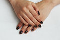 beauty delicate coffee manicure with gold sparkles with gel varnish on a white wall background Royalty Free Stock Photo