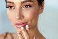 Beauty Face. Beautiful Woman Touching Lips With Lip Balm On Royalty Free Stock Photo
