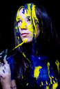 Beauty fashion close up portrait of woman painted blue and yellow with brushes and paint on black background Royalty Free Stock Images