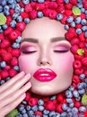Beauty fashion model girl lying in fresh ripe fruits, berries and mint. Face in colorful berries close-up. Beautiful make-up Royalty Free Stock Photo