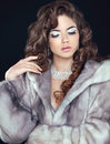 Beauty Fashion Model Woman in Mink Fur Coat. Winter Brunette Girl in Luxury clothes. Long wavy hair. Makeup. Jewelry. Royalty Free Stock Photo