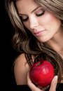 Beauty female portrait holding apple isolated over black background Royalty Free Stock Image