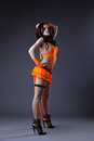 Beauty girl dance in orange go-go costume Royalty Free Stock Photography