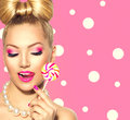 Beauty girl eating colourful lollipop over polka dots background Stock Photos