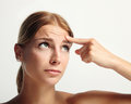 Beauty girl with first wrinkle young showing finger her in forehead Royalty Free Stock Photography