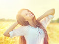 Beauty girl on summer field in white dress having fun Royalty Free Stock Photography