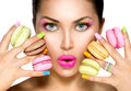 Beauty girl taking colorful macaroons