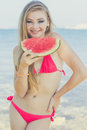 Beauty girl is wearing swimsuit eating watermelon Royalty Free Stock Photo