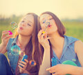 Beauty girls blowing soap bubbles in spring park Royalty Free Stock Photo