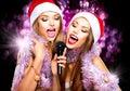 Beauty girls in santa hats singing Royalty Free Stock Photo