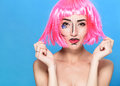 Beauty head shot. Young woman with creative pop art make up and pink wig looking at the camera on blue background Royalty Free Stock Photo