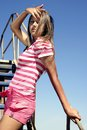 Beauty on the ladder touches hair young over sky Royalty Free Stock Photo