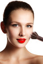 Beauty model with makeup Brush. Bright make-up for brunette woman with blue Eyes. Red lips. Beautiful Face. Perfect Skin.