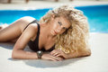 Beauty model summer portrait sexy blond tanned woman sunbathing by blue water swimming pool girl with curly hair posing at sunny Royalty Free Stock Image
