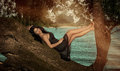 Beauty model in tree by water Royalty Free Stock Photo