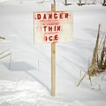 Beauty in nature warning sign of thin ice at lakeside orangeville dufferin county ontario canada Stock Photography