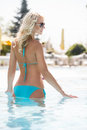 Beauty in pool rear view of beautiful young women in bikini sta woman standing and smiling Royalty Free Stock Images