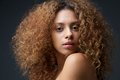 Beauty portrait of a beautiful female fashion model with curly hair close up Royalty Free Stock Photo