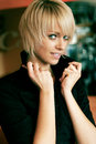 Beauty portrait of a beautiful young blond woman with short hair holding up the collar the shirt Stock Photos