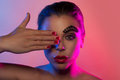 Beauty portrait of a woman covering the eye beautiful her right with hand in pink and purple lights with avant garde makeup Stock Photos