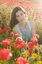Beauty posing into the flowers brunette girl in field amongst Stock Photos