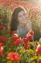 Beauty posing into the flowers brunette girl in field amongst Royalty Free Stock Images