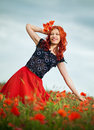 Beauty redheaded woman in poppy field Stock Photos