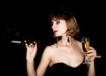 Beauty retro female model with professional makeup holding mouthpiece and glass of champagne. fashion vintage woman on a Royalty Free Stock Photo