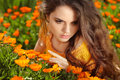 Beauty romantic girl outdoors beautiful teenage model girl pos posing over marigold flowers field enjoyment Stock Image