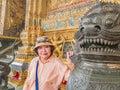 Beauty senior women with Thai lion statue in wat phrakaew Temple bangkok Thailand Royalty Free Stock Photo