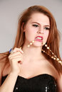 Beauty shot of young woman fashion beautiful biting on necklace Royalty Free Stock Photo