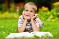Beauty smiling child boy reading book outdoor on green grass field Stock Image