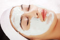 Beauty treatment in spa salon woman with facial clay mask Stock Photography
