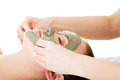Beauty treatment in spa salon woman with facial clay mask on white Stock Photography