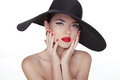Beauty vogue style fashion model girl in black hat manicured na nails and red lipstick isolated on a white background Stock Images