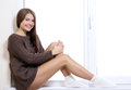 Beauty on the window sill beautiful young woman sitting and looking through Royalty Free Stock Photos