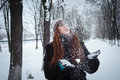 Beauty winter girl blowing snow in frosty winter park flying snowflakes joyful young redhead woman having fun Royalty Free Stock Photos