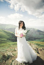 Beauty woman, bride with perfect white dress posing on the rock background mountains Royalty Free Stock Photo