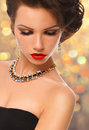 Beauty Woman with Perfect Makeup and luxury accessories on gold background Royalty Free Stock Photo