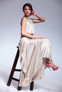 Beauty woman posing on a high stool Royalty Free Stock Photo