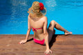 Beauty woman sitting on edge of swimming pool a young wearing a red bikini and pamela a backward Stock Photos