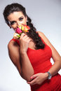 Beauty woman smells roses young smelling some while looking into the camera on gray background Royalty Free Stock Image