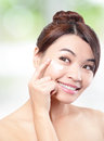 Beauty young woman applying cosmetic cream under eyes concept for eye and skin care asian Stock Image